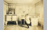 Shaw Bros. Creamery Laboratory with unidentified woman (019-012-677)