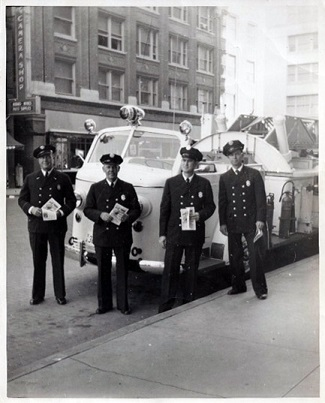 Captain Asbury Bice and other members of the Fort Worth Fire Department stand in front of ladder truck in the mid-1950s across the street from The Camera Shop, 709 Throckmorton - believed to be the first ladder truck in the FWFD