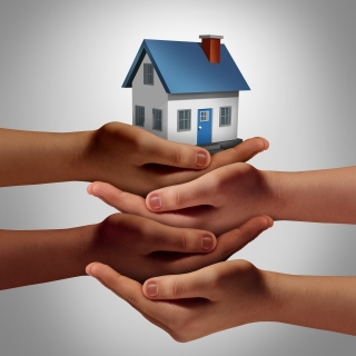 Diverse hands holding a house