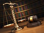 scales and gavel on desk with colorful books in the background