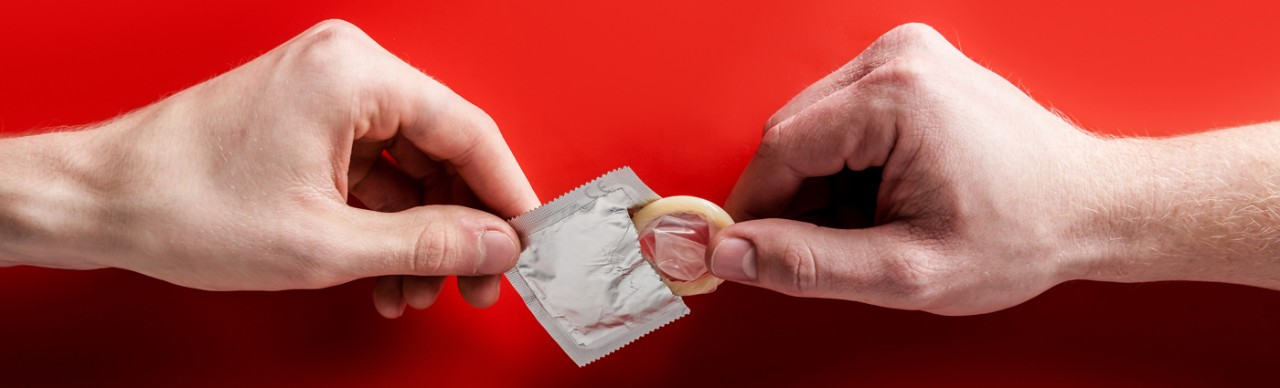 hands pulling condom package open