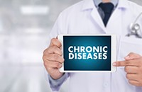 man in labcoat holding tablet saying Chronic Diseases