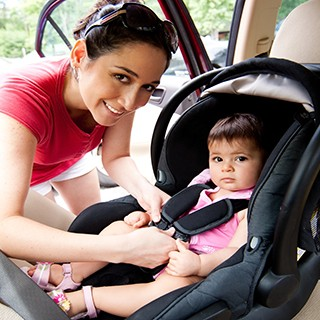 ethnic mother strapping child into car seat